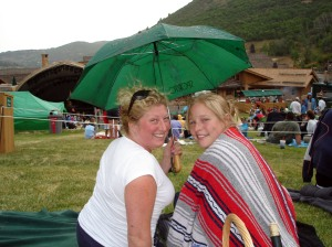 kim and laura share some wine and an umbrella